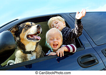 Happy Children and Dog in Minivan - Two happy little...