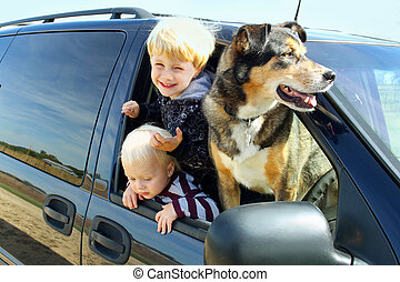 Children and Dog in Minivan - wo happy young children and...