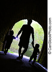 Father and Children Exploring Dark Tunnel - a father and his...