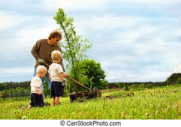Family Planting Tree - a young father and his two children...