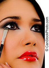 portrait of beautician doing eye make up of woman