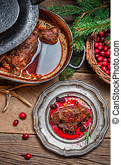 Roast venison with cranberry sauce and served in the...