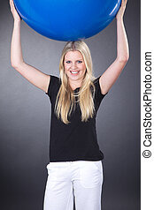 woman lifts exercise ball