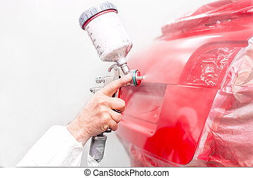 auto engineer paiting a red paint on modern car in special...