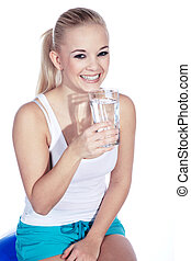young woman sitting on ball and drinking water