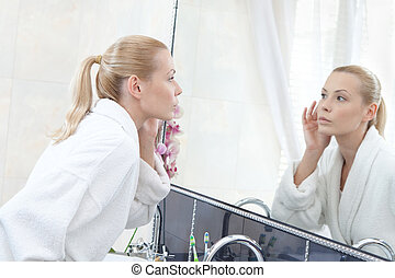 Woman looks at her self in mirror - Woman in bathrobe looks...