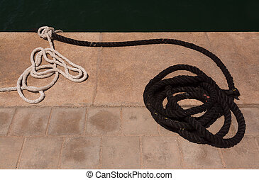 Mooring ropes on jetty - Empty mooring ropes in black and...