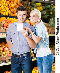 Happy couple with shopping list against the piles of fruits...