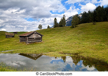 old wooden hut by lake in Alps