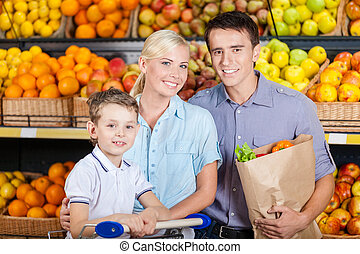 Happy family against shelves of fruits goes shopping. Father...