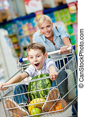 Little boy sits in the shopping trolley with watermelon and...