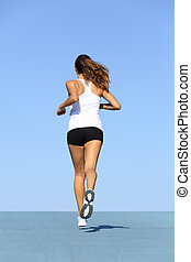 Back view of a fitness woman running on blue with the...