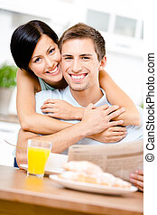 Woman hugs eating boyfriend who sits at the kitchen table...