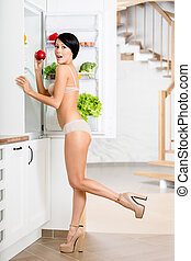 Full length of woman near the opened refrigerator full of...