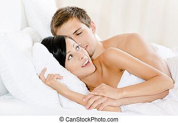 Man lying in bed embraces woman - Man lying in bed with...