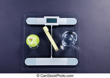bathroom scale with tape measure and apple water