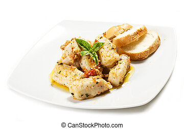 hake cooked in a pan with tomatoes on a white background