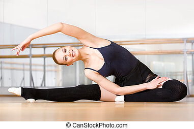 Bending female ballet dancer stretches herself on the wooden...