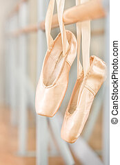 Close up of pointes for ballet hanging on barre - Close up...