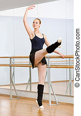 Ballet dancer dancing near barre in studio - Wearing leotard...