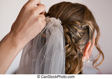 Bride with white veil - Placing the pin on a wedding...