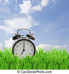 time concept - alarm clock in grass on blue sky