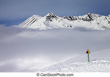 Warning sing on ski slope and mountains in fog Caucasus...
