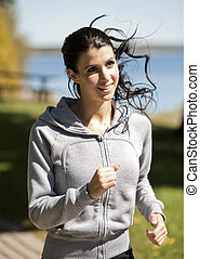 woman running - brunette fitness woman is running in the...