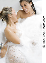 into foam togheter - one blond girl and one brunette in the...