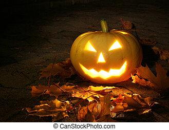Halloween pumpkin in dark garden - Halloween pumpkin glowing...