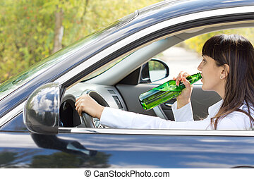 Inebriated female driver drinking alcohol directly from the...