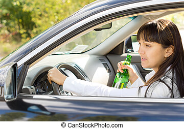 Happy inebriated female driver holding a botttle of alcohol...