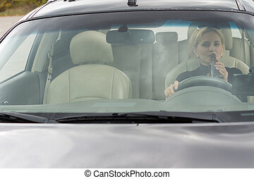 Female driver drinking alcohol in the car - View through the...