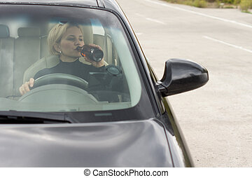 Drunk woman driving and drinking - View through the front...