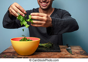 Young man is a happy salad tosser