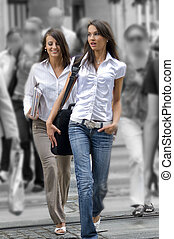 crossing people - two young women between the crowd crossing...