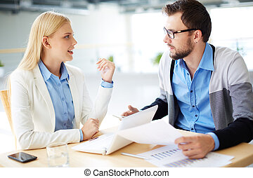 Consulting - Two business people discussing plans or project...
