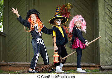 Halloween girls on broom - Portrait of three Halloween girls...