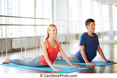 Stretching practice - Portrait of young woman and man doing...