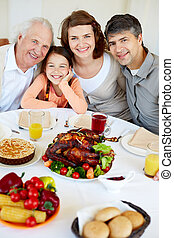 Thanksgiving joy - Portrait of happy family sitting at...
