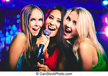 In karaoke bar - Portrait of happy girls singing in...