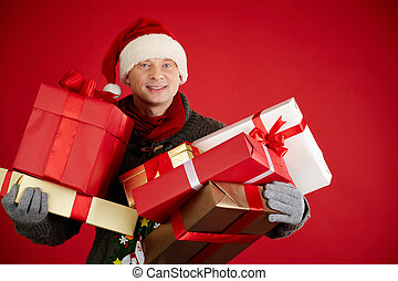 Christmas gifts - Portrait of happy man in Santa cap holding...