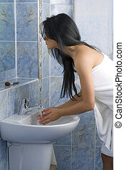 like every day - sensual brunette washing her face with...