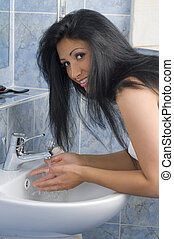 every day - sensual brunette washing her face with water in...