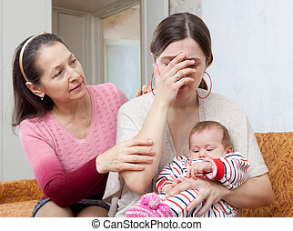 Mature woman comforts crying daughter with baby - Mature...
