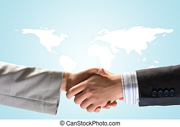 Two businessmen shaking hands on a background map of the...