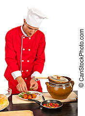 Chef man garnish plate with food against white background