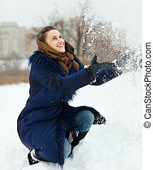 Girl throwing up snowflakes in wintry park