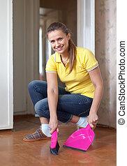 Woman sweeping the floor - Woman sweeping the floor at home...