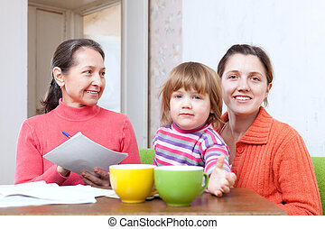 Family calculates the family budget - Mature woman and adult...